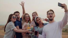 A empresa amigável está no ar livre, bebe os cocktail deliciosos, sorrindo e tomando selfies Movimento lento, verão urbano video estoque