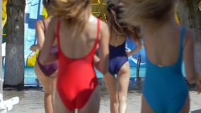 A empresa da fêmea nova em maiôs brilhantes corre aos waterslides no parque da água no tempo vídeos de arquivo