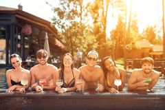 A empresa de amigos felizes bebe bebidas do cocktail na associação no verão Partido de piscina imagens de stock royalty free