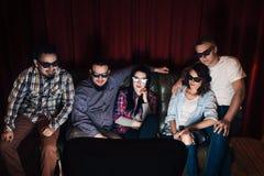 A empresa de cinco amigos nos vidros 3d olha a tevê Imagens de Stock Royalty Free