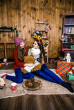 Empresa de duas meninas com os presentes na sala com paredes de madeira Fotografia de Stock Royalty Free