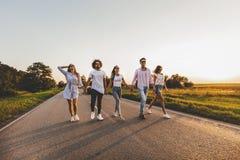 A empresa de indivíduos à moda novos felizes anda em uma estrada secundária em um dia ensolarado imagem de stock