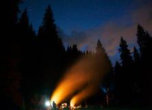 A empresa de jovens está sentando-se em torno da fogueira e músicas do canto Acampamento do turista sob o céu noturno estrelado c Imagem de Stock