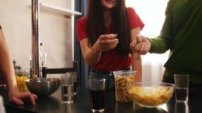 Empresa de quatro amigos novos que passam o tempo que está junto na cozinha Jogando as tesouras de papel da rocha video estoque