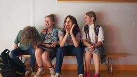 A empresa dos adolescentes com as sacolas no corredor da escola As crianças sentam-se no banco e para ter a fala do divertimento video estoque