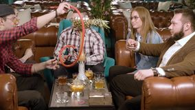 Empresa dos amigos que conversam e que fumam o cachimbo de ?gua no caf? video estoque