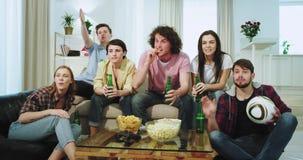 Empresa grande do close up de multi étnico do amigo na frente da cerveja bebendo e de olhar da tevê um fósforo de futebol eles ap vídeos de arquivo