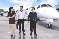 Empresaria árabe con sus amigos cerca de un aeroplano fotos de archivo