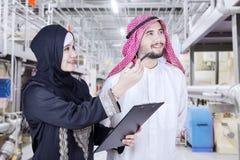 Empresaria árabe y su socio en fábrica imagenes de archivo