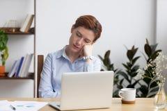 Empresaria aburrida que duerme a mano sent?ndose en el escritorio de oficina imagen de archivo libre de regalías