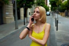 Empresaria acertada que habla en el teléfono elegante mientras que se coloca en la calle de la ciudad en verano Foto de archivo