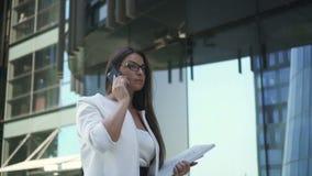 Empresaria acertada que habla en el teléfono mientras que camina metrajes