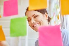 Empresaria acertada sonriente que recolecta ideas Imágenes de archivo libres de regalías