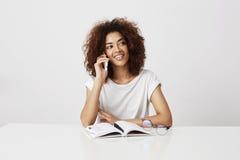 Empresaria africana alegre hermosa que habla en el teléfono sobre el fondo blanco Imágenes de archivo libres de regalías