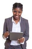 Empresaria africana de risa que trabaja con la tableta Imagen de archivo libre de regalías