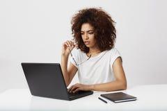 Empresaria africana que mira la pantalla del ordenador portátil que piensa sobre el fondo blanco Fotografía de archivo libre de regalías
