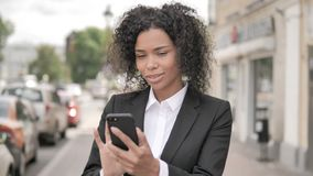 Empresaria africana Using Smartphone Standing al aire libre en el sendero almacen de video