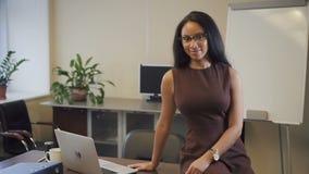 Empresaria afroamericana atractiva que sonríe en oficina de lanzamiento
