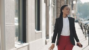 Empresaria afroamericana feliz joven en auriculares que camina la calle de la ciudad mientras que escucha la música en metrajes