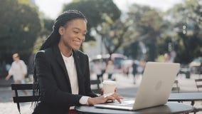 Empresaria afroamericana sonriente que se sienta en café en la terraza del verano, el café de consumición y hablando en el vídeo metrajes