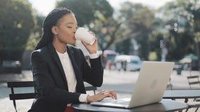 Empresaria afroamericana sonriente que se sienta en café en la terraza del verano, el café de consumición y trabajando en el orde metrajes