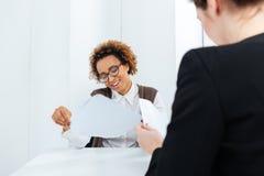 Empresaria afroamericana sonriente que tiene uso de la entrevista y del relleno de trabajo fotos de archivo libres de regalías