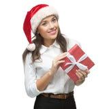 Empresaria alegre joven en el sombrero de santa que sostiene el regalo de la Navidad Imagenes de archivo