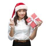 Empresaria alegre joven en el sombrero de santa que sostiene el regalo de la Navidad Imagen de archivo libre de regalías