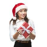 Empresaria alegre joven en el sombrero de santa que sostiene el regalo de la Navidad Imágenes de archivo libres de regalías