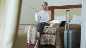 Empresaria alegre que habla el teléfono móvil y que escribe notas en libreta mientras que se sienta en cama en la habitación Viaj almacen de video
