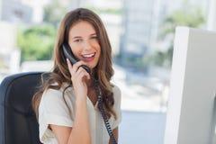 Empresaria alegre que tiene una conversación telefónica Imágenes de archivo libres de regalías