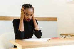 Empresaria americana africana o negra pensativa preocupante que se sostiene la cara bonita con las manos, oídos cerrados imagen de archivo