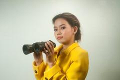 Empresaria asiática bastante joven en el traje amarillo sosteniendo los prismáticos. Fotografía de archivo
