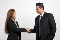 Empresaria asiática bonita que sacude al hombre de negocios de las manos para sellar un trato con su socio en un fondo blanco imagen de archivo