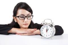 Empresaria asiática con el reloj de alarma Imagenes de archivo