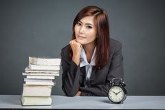 Empresaria asiática con un reloj y los libros Imagen de archivo libre de regalías