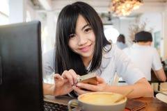 Empresaria asiática del inconformista que trabaja en el ordenador portátil con la taza de café Fotografía de archivo