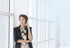 Empresaria asiática en el teléfono en oficina imagenes de archivo