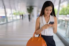 Empresaria asiática hermosa joven que cuelga hacia fuera en el footbridg Fotos de archivo libres de regalías