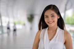 Empresaria asiática hermosa joven que cuelga hacia fuera en el footbridg Foto de archivo libre de regalías