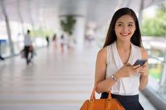Empresaria asiática hermosa joven que cuelga hacia fuera en el footbridg Imagen de archivo libre de regalías