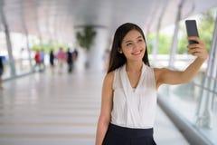 Empresaria asiática hermosa joven que cuelga hacia fuera en el footbridg Foto de archivo