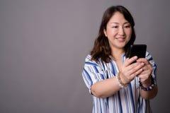 Empresaria asiática hermosa madura que usa el teléfono móvil imagen de archivo libre de regalías