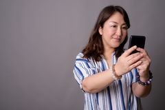 Empresaria asiática hermosa madura que usa el teléfono móvil fotografía de archivo libre de regalías