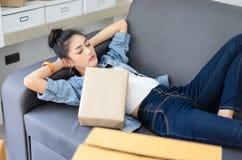 Empresaria asiática joven cansada que miente en la cama con la caja de embalaje de la caja de embalaje, de la carga del trabajo e imagenes de archivo
