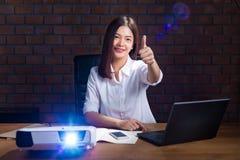 Empresaria asiática joven en la camisa del color del ligth que trabaja tarde en h imagen de archivo libre de regalías