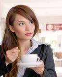 Empresaria asiática joven que come la taza de café Foto de archivo libre de regalías