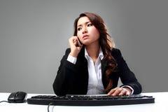 Empresaria asiática joven que habla en el teléfono mientras que mecanografía Foto de archivo