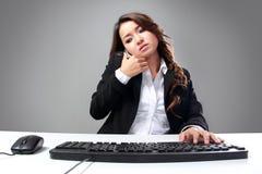 Empresaria asiática joven que habla en el teléfono mientras que mecanografía Imagenes de archivo