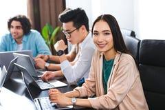 empresaria asiática joven que mira la cámara la tabla con los ordenadores portátiles y los hombres de negocios que trabajan detrá imagenes de archivo